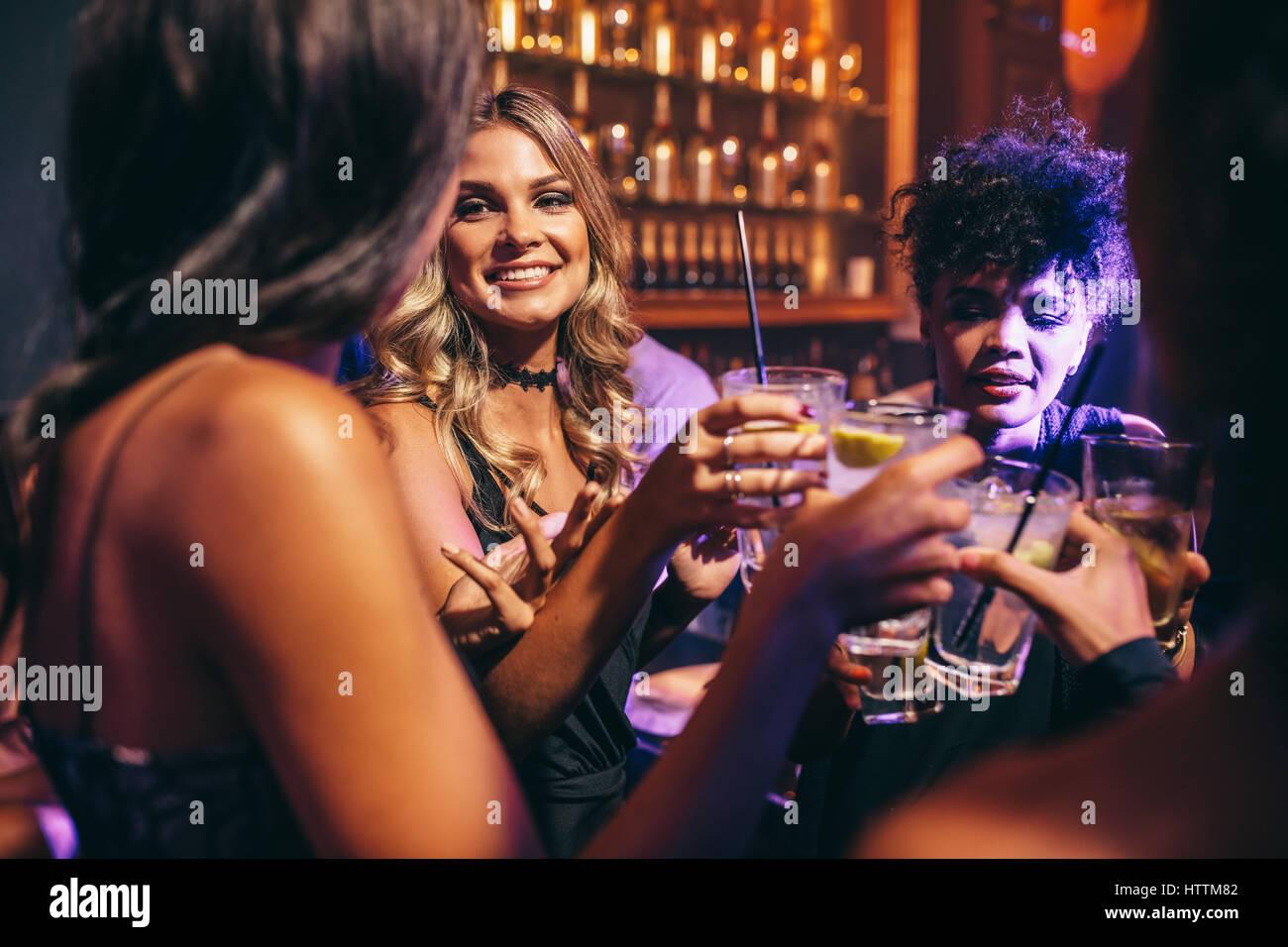Groupe d'amis ayant des boissons à la discothèque. Les jeunes bénéficiant dans un bar. Photo Stock