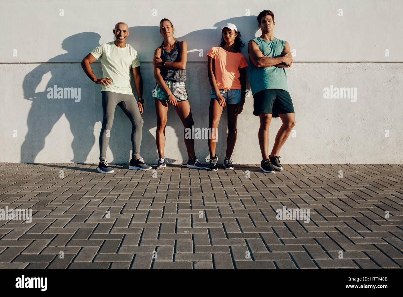 Longueur totale shot of young friends posing together. Groupe de personnes debout remise en forme par un mur extérieur. Photo Stock