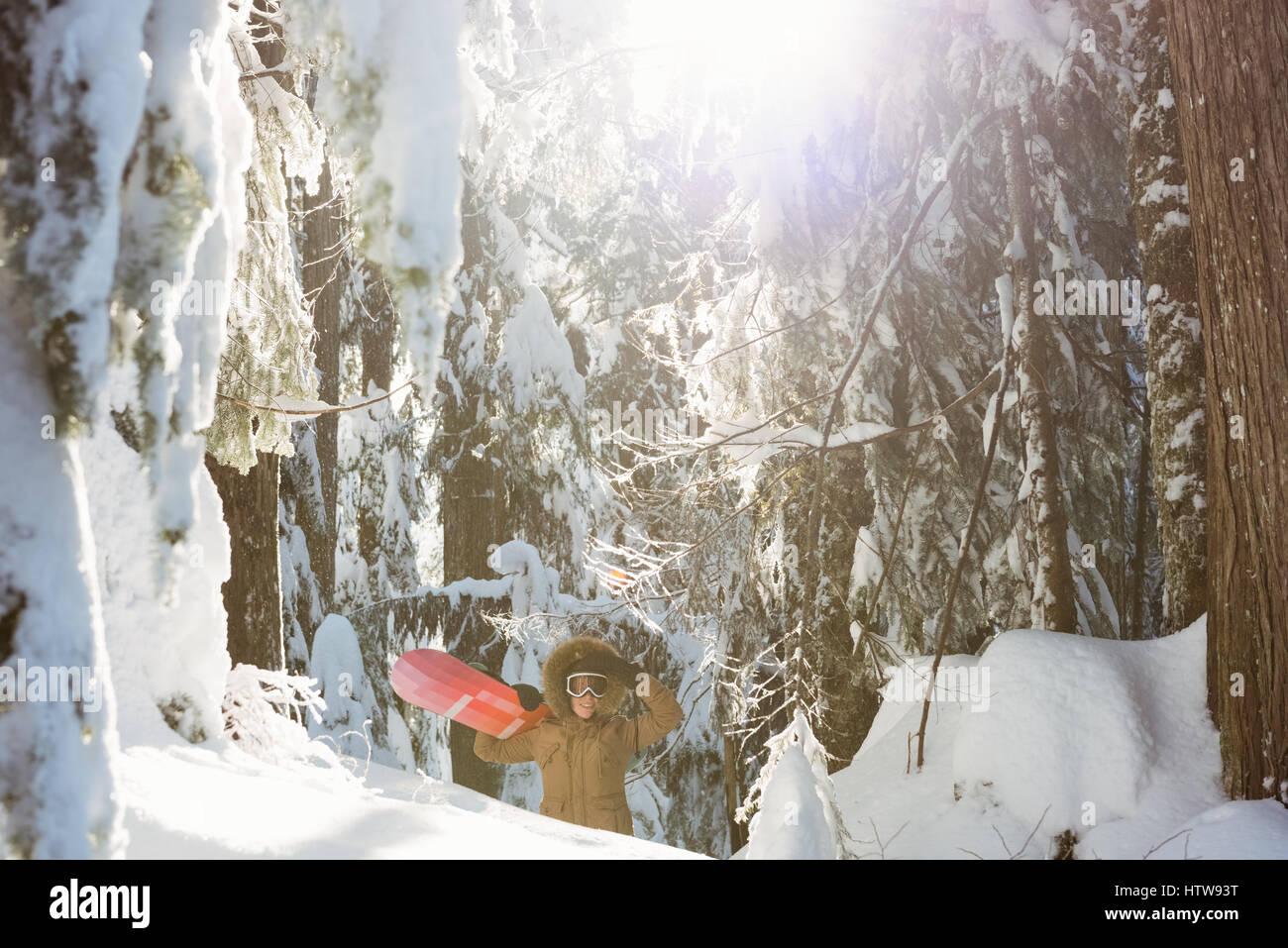 Femme avec snowboard marche sur la montagne enneigée Photo Stock