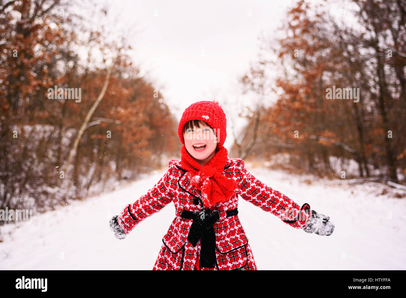 Girl standing in winter forest with arms outstretched Banque D'Images
