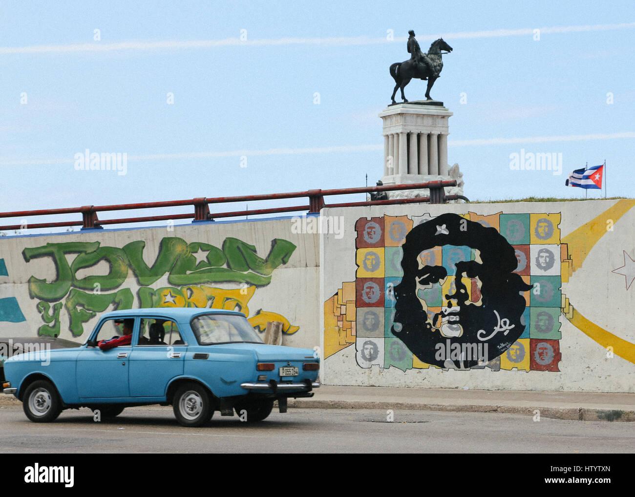 Une vieille voiture Lada bleu vu sur la route par le monument Maximo Gomez et street art représentant Che Guevara à la Havane, Cuba Banque D'Images