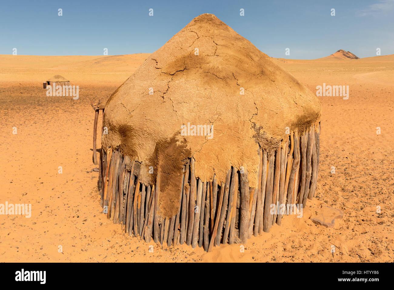 Une habitation hut dans un village Himba dans le désert aride du Kaokoland, Namibie Banque D'Images