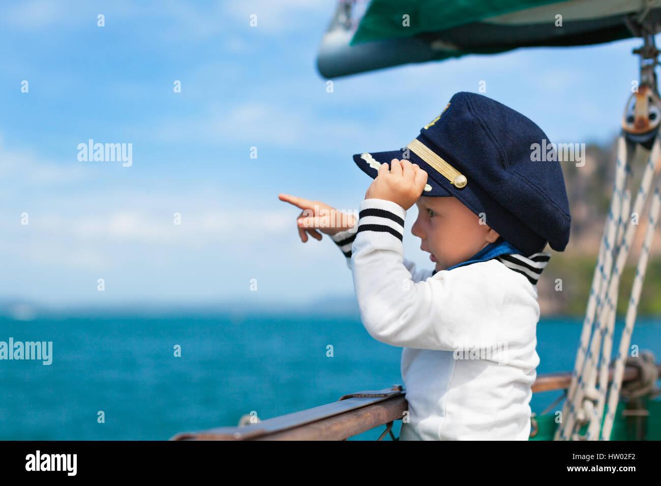 Funny little baby le capitaine à bord du yacht à regarder la mer au large de l'été sur une Photo Stock