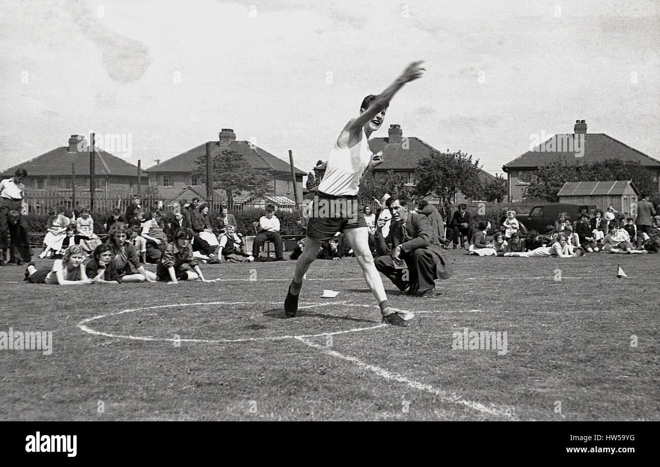 Années 1940, jette le discus d'écolier dans une école sports le jour, en Angleterre. Photo Stock