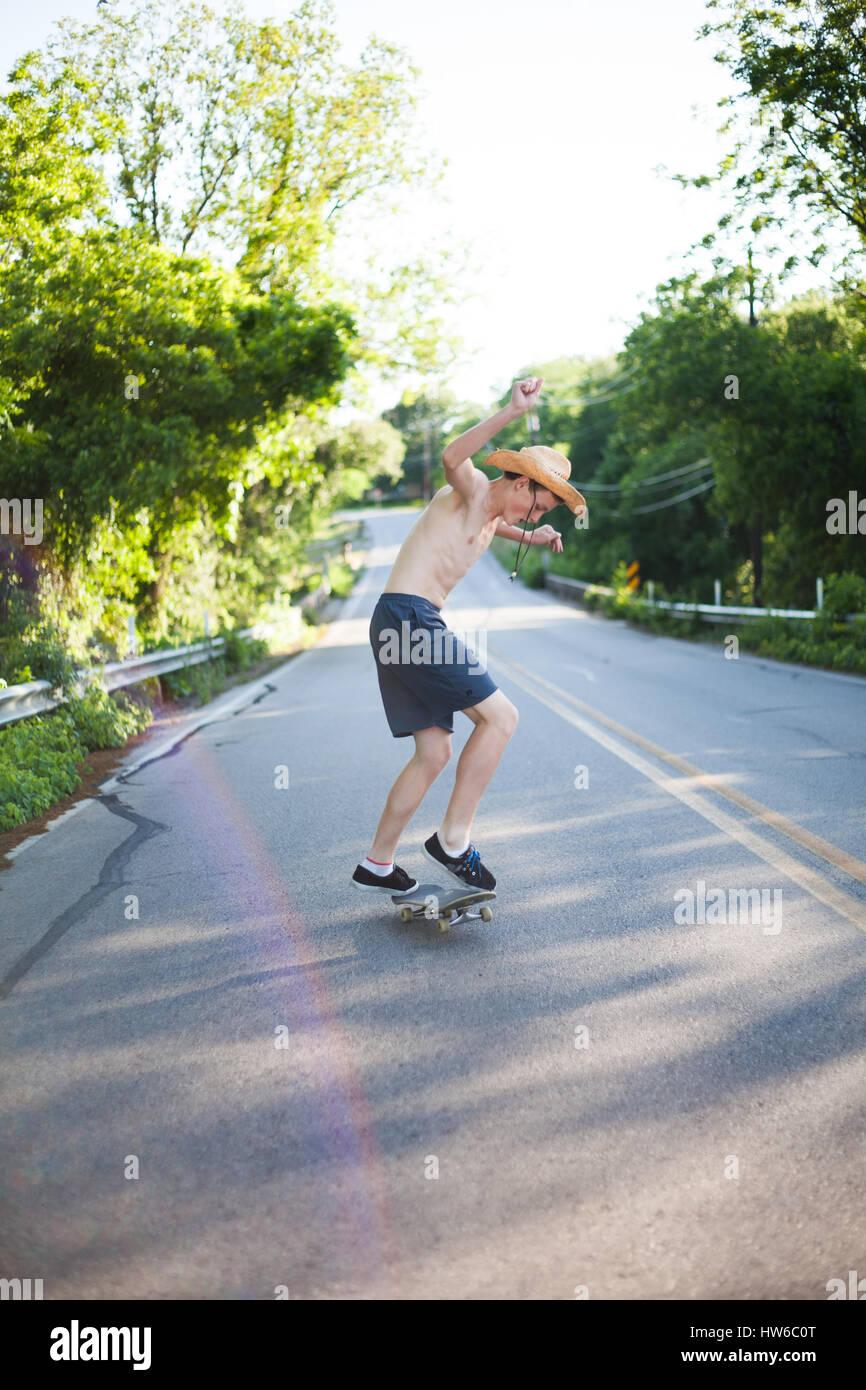 Boy skateboarding en bas de la route Photo Stock