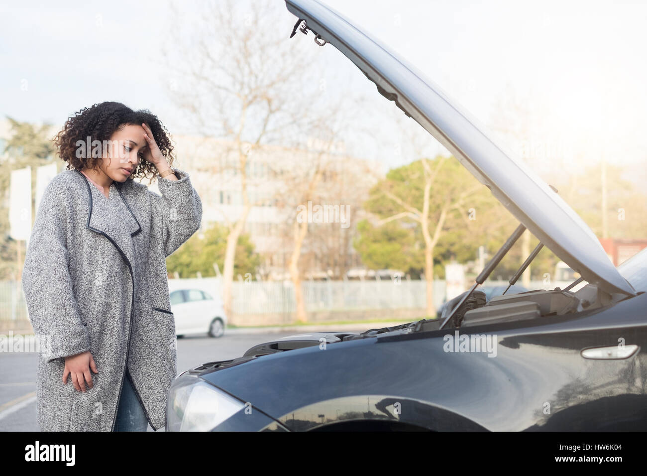 Femme désespérée après avoir vérifié sa voiture moteur cassé Photo Stock