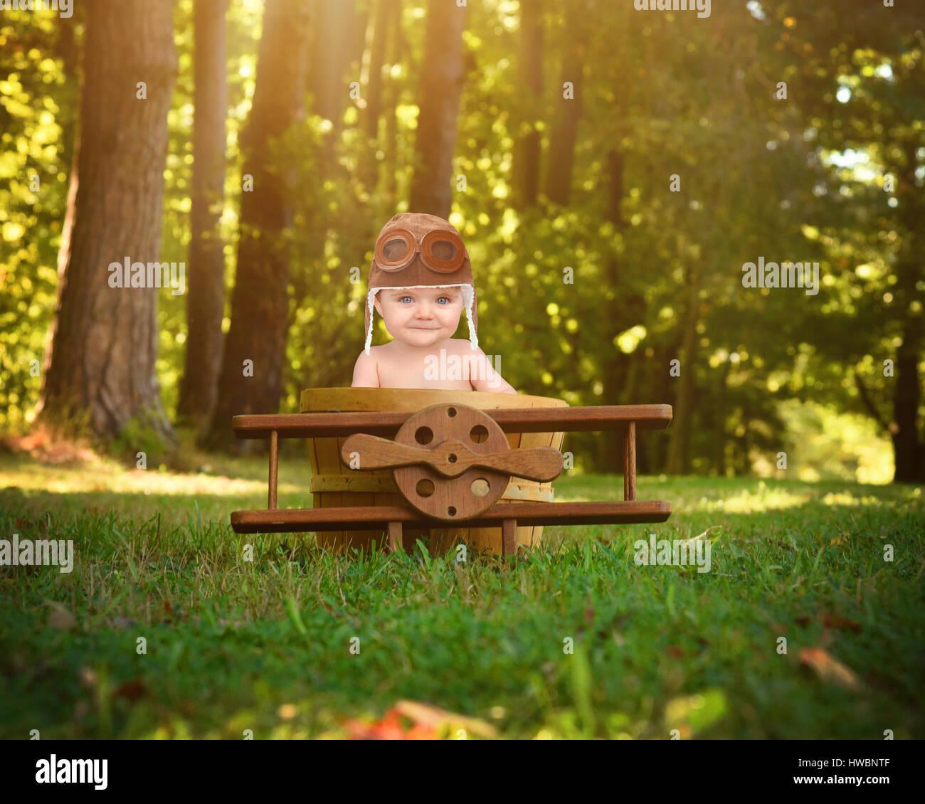 Un petit bébé est assis dans un avion en bois panier prop dans le parc faisant semblant de voyager et de prendre l'avion avec un pilote pour un chapeau sur la créativité ou d'imagination Banque D'Images