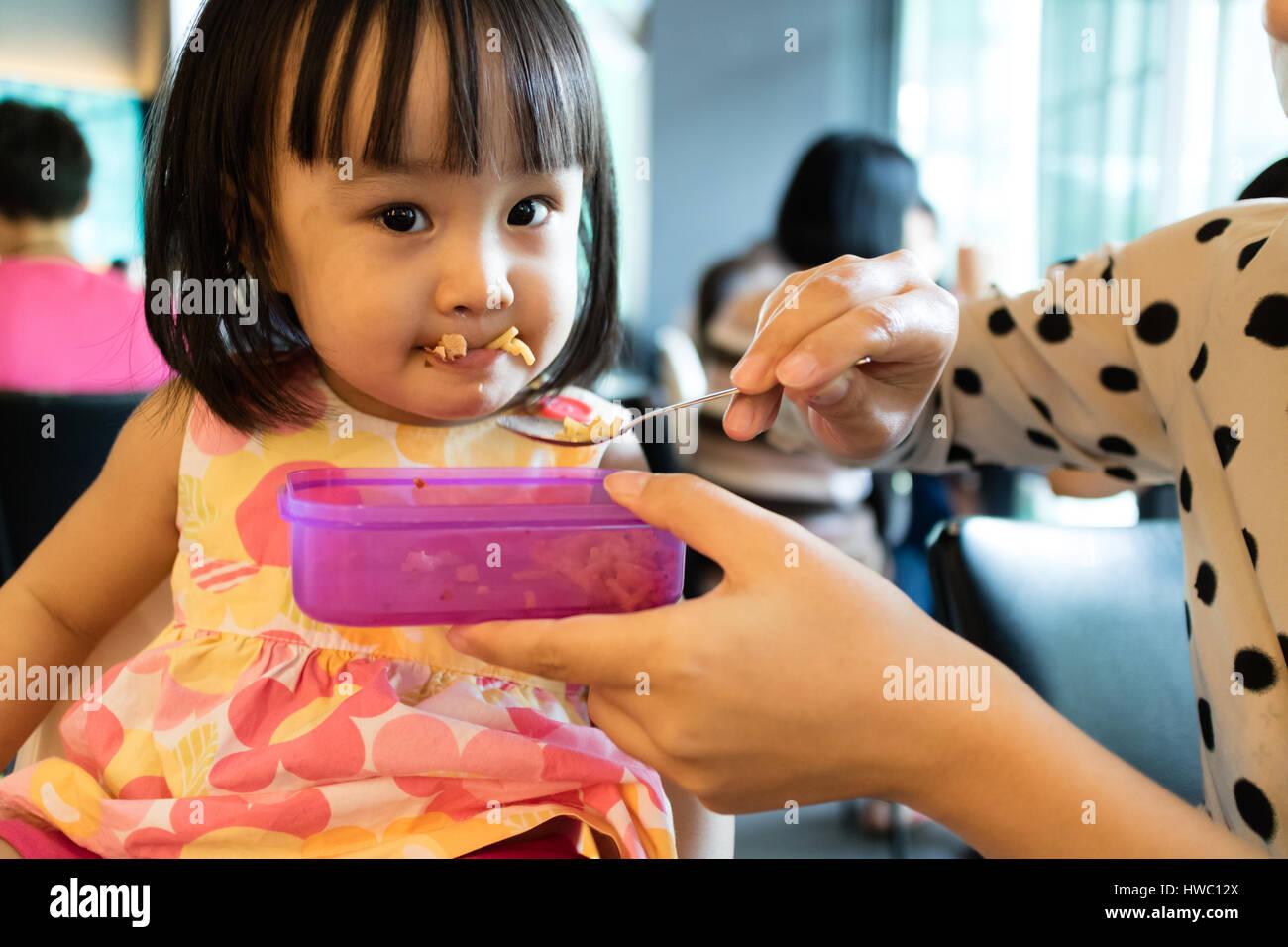 Mère fille asiatique alimentation Aliments pour enfants dans un restaurant. Photo Stock