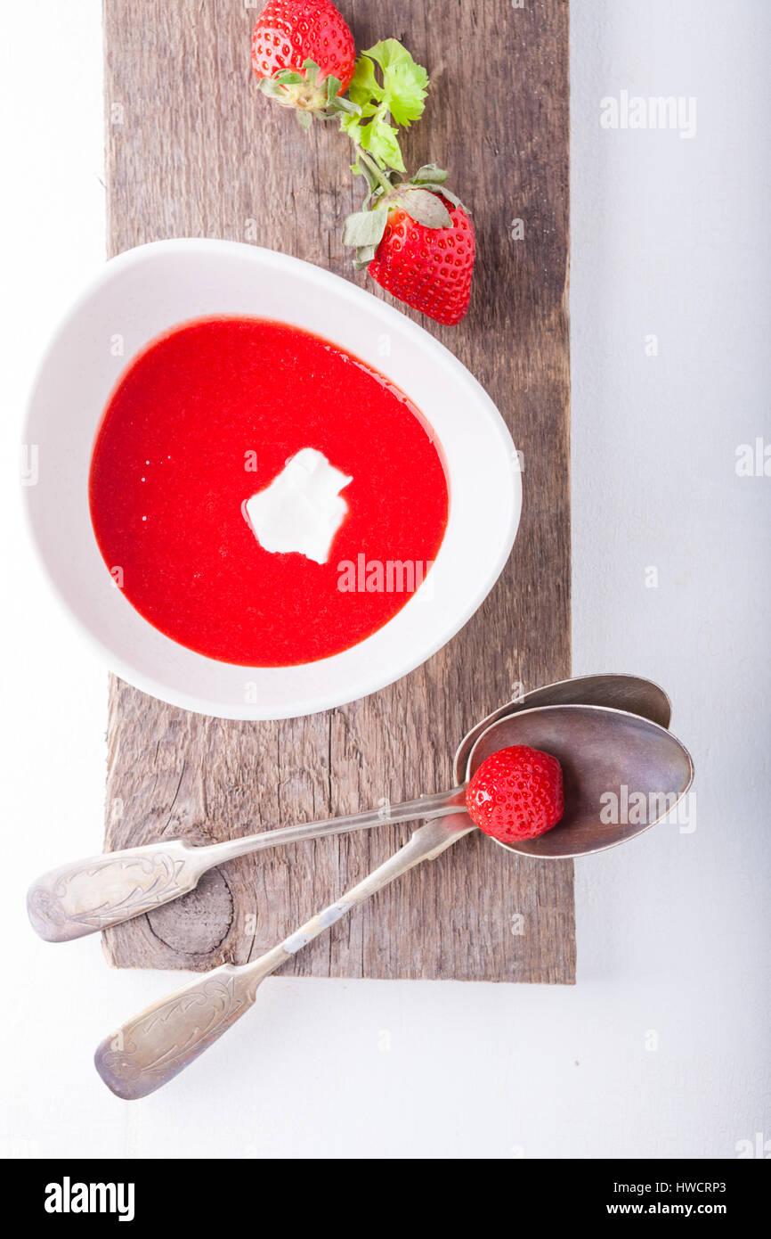 Soupe de fraises avec une cuillère sur une table. Photo Stock