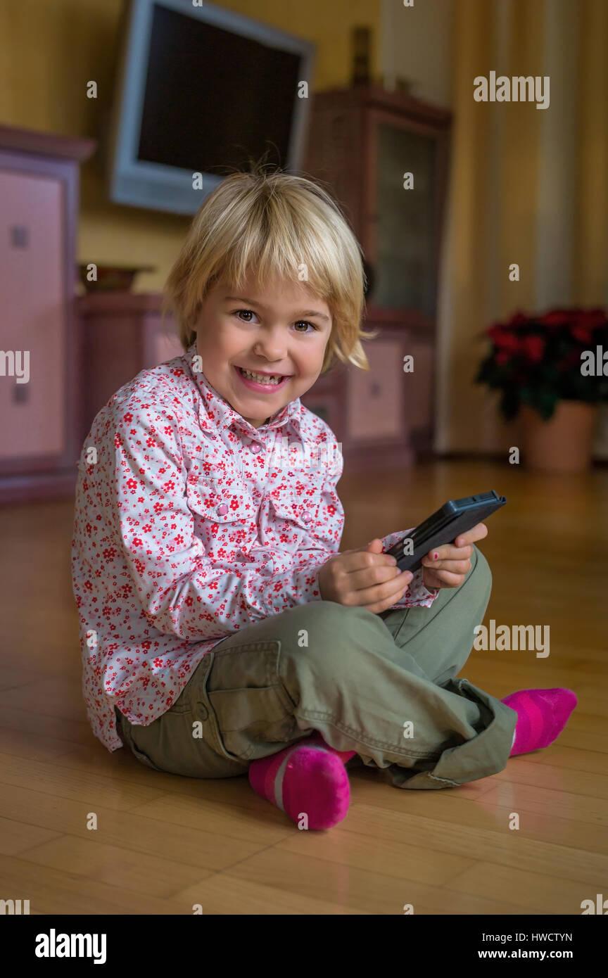 Un enfant joue avec un téléphone mobile. Téléphone mobile pour enfants, Ein genre spielt mit la main. Mobiltelefon für Kinder Banque D'Images