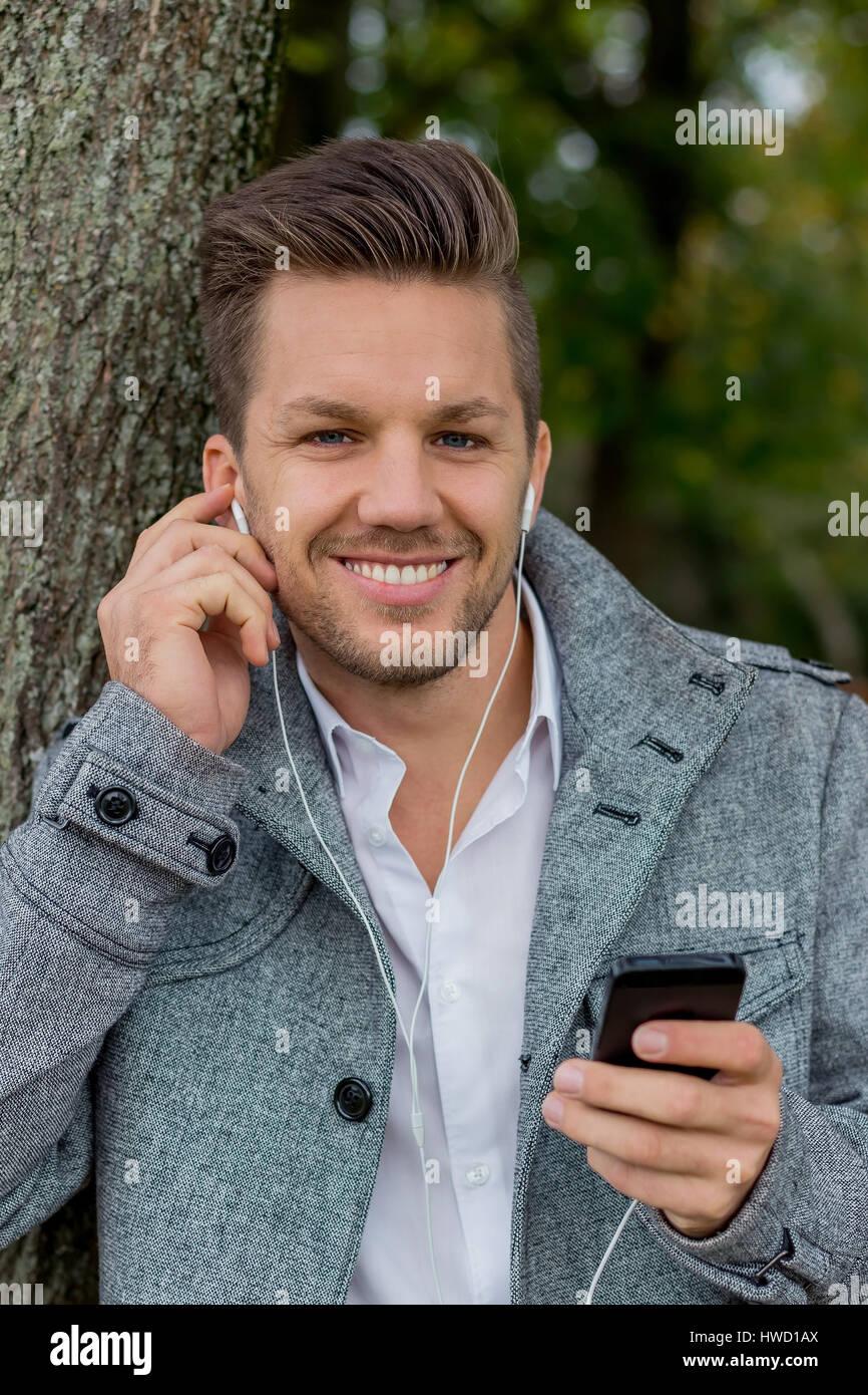 Un homme entend la musique avec votre téléphone mobile. Le divertissement sur le téléphone mobile., Ein Mann hört Musik mit Ihrem Handy. Unterhaltung suis Mobiltelefon. Banque D'Images