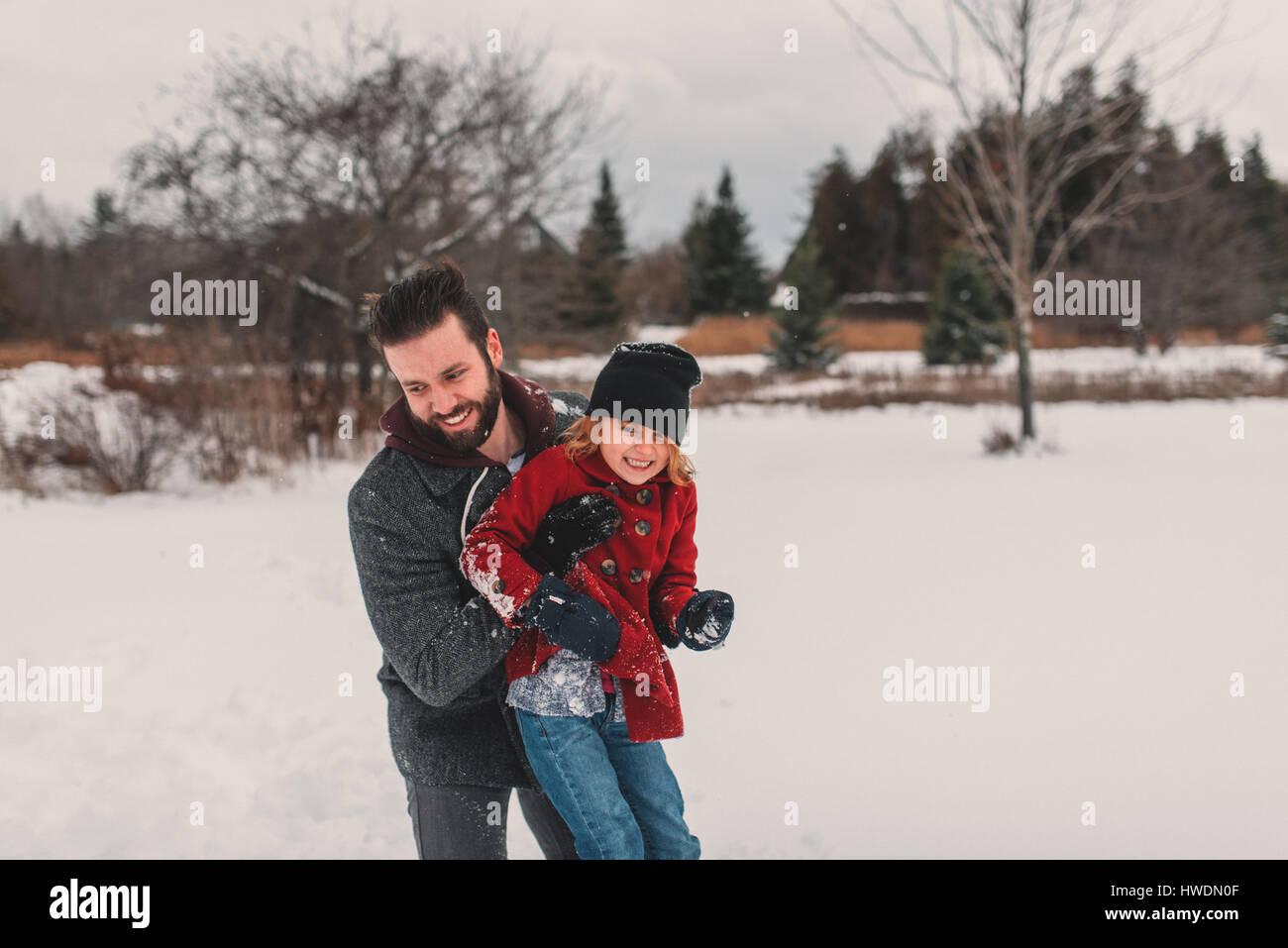 Père et fille jouent dans la neige Photo Stock