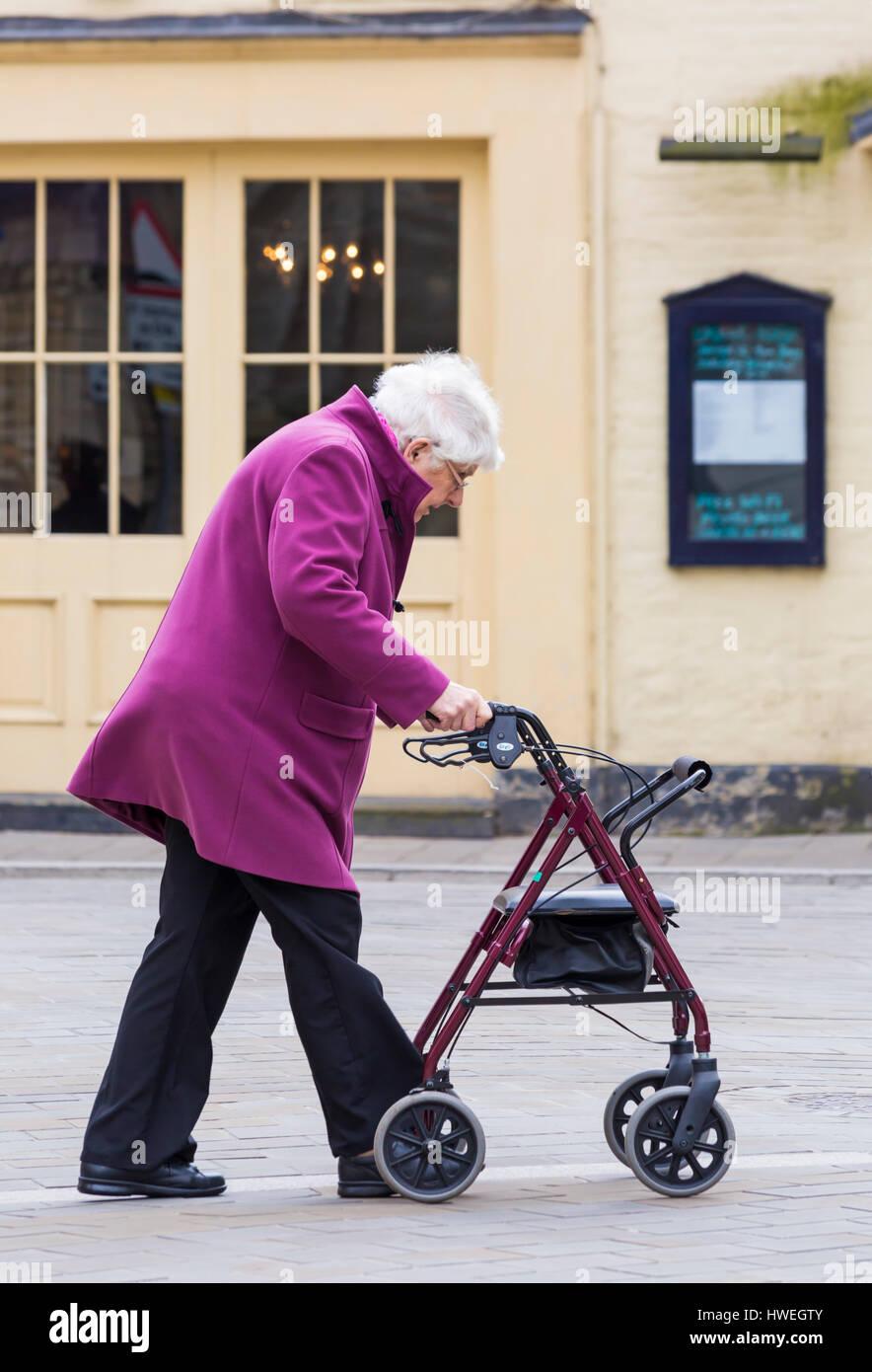 Femme âgée poussant le long du châssis à l'aide à la mobilité partager l'espace Photo Stock