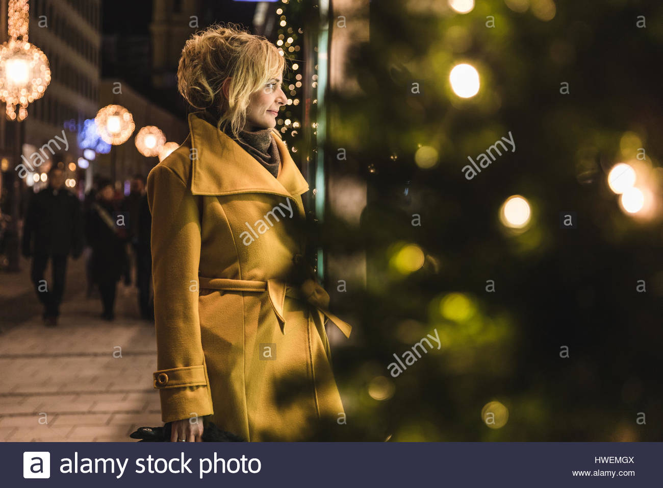 Young woman window shopping de Noël dans la nuit, Munich, Allemagne Photo Stock