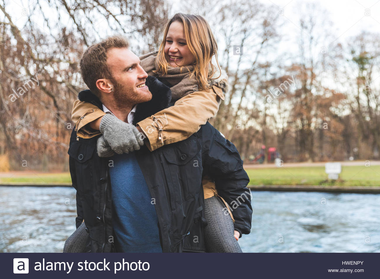 Young woman getting piggyback de copain sur Riverside Park Photo Stock