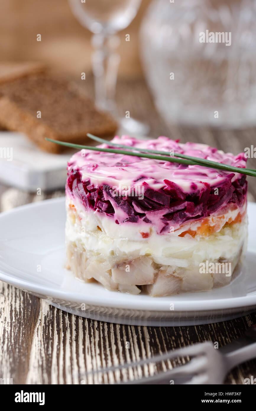 Vêtus faits maison, hareng mariné hareng salade en couches traditionnel russe sous un manteau de fourrure Photo Stock