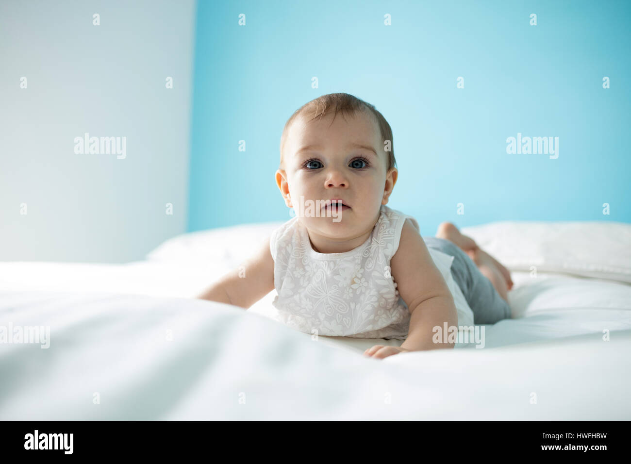 Portrait of cute baby girl on lit dans la chambre Banque D'Images