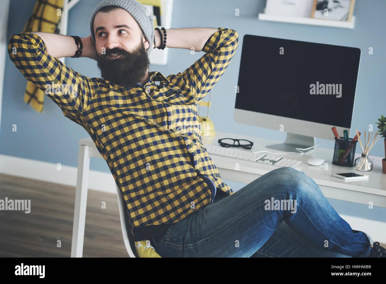 L'homme d'affaires de vous coucher sur un chaise à côté d'ordinateur Photo Stock