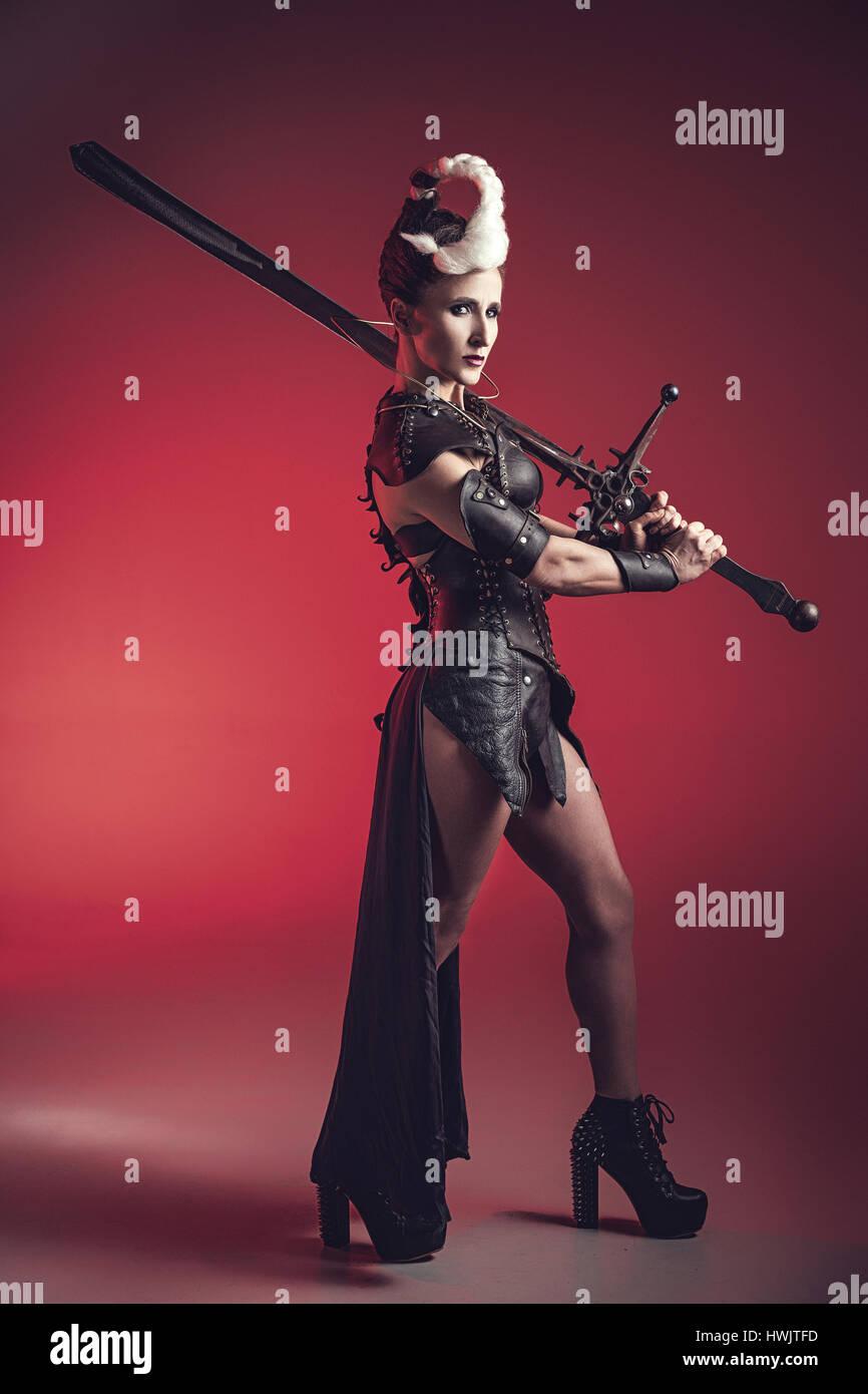Belle femme guerrière. Chasseur de fantaisie. La princesse ou la reine en cuir corset prêt pour la guerre. Lumière rouge et blanc arme. Banque D'Images