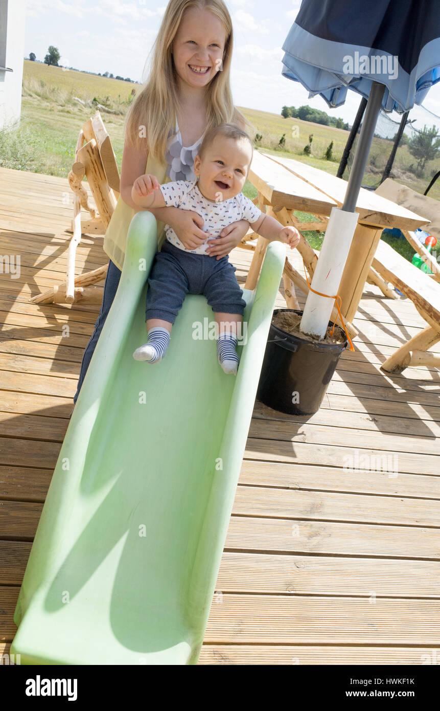 Aider sœur frère bébé en bas de la diapositive. Polish les enfants de 8 et 7 mois d'avoir du plaisir. Zawady Europe Banque D'Images