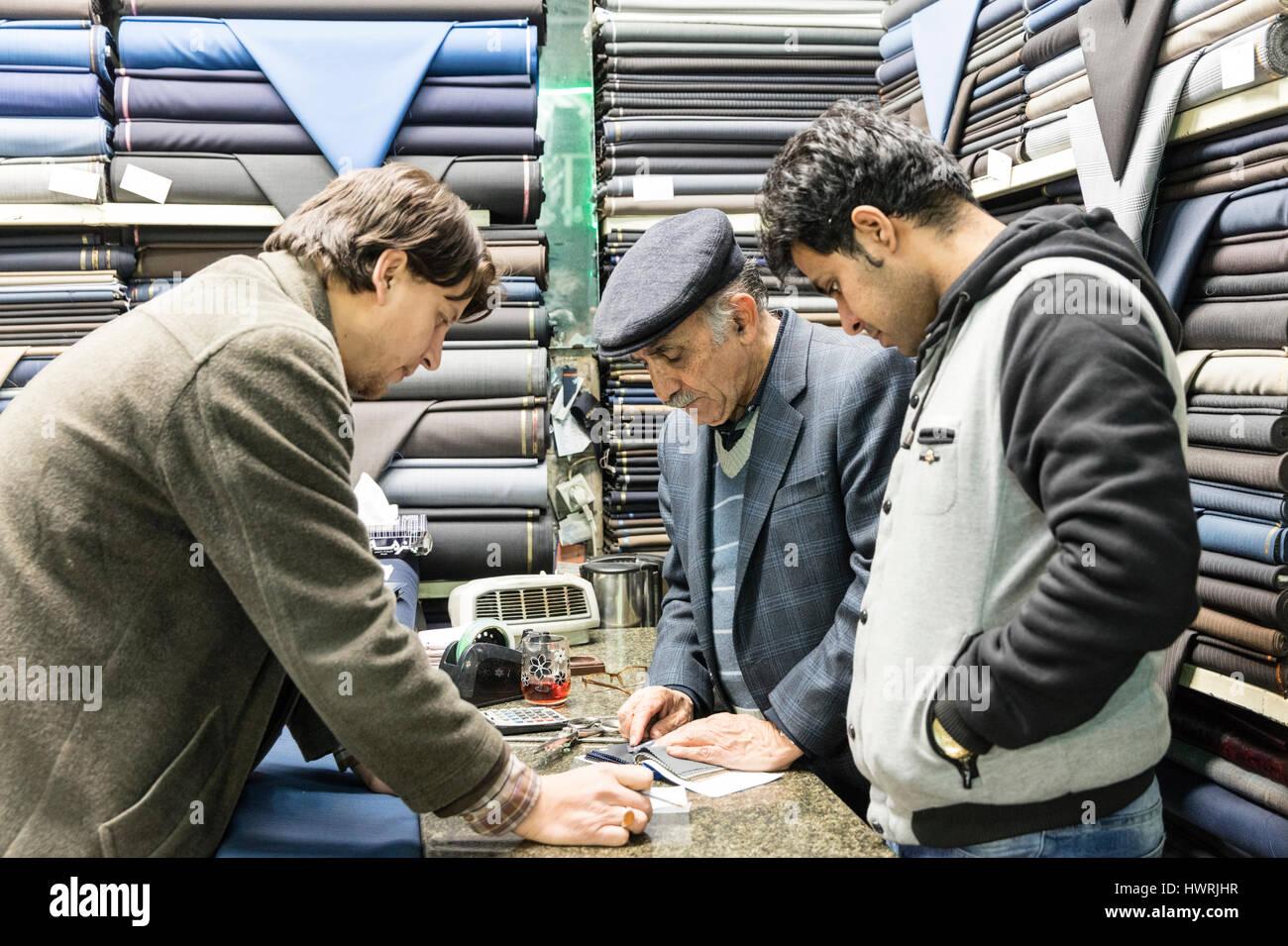 Vendeurs et clients entouré par vis de la laine en tissu tissu au logement du bazar de Téhéran Photo Stock