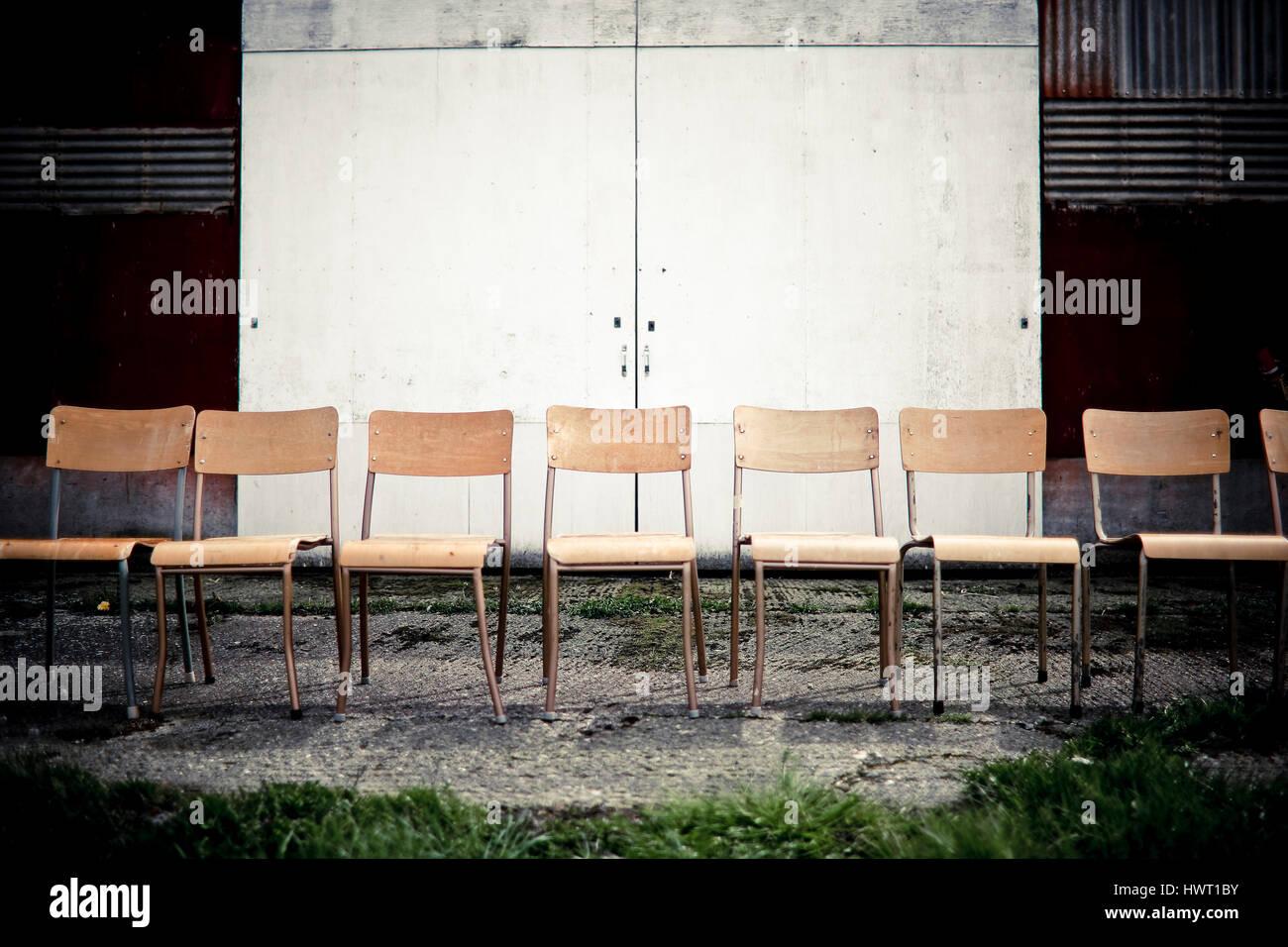 Chaises vides sur sentier contre porte fermée Banque D'Images