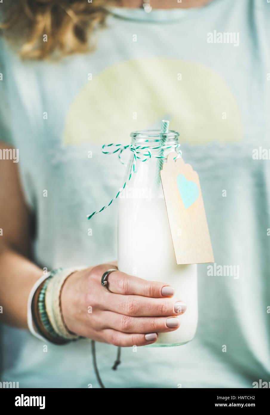 Jeune femme tenant une bouteille de lait d'amande sans produits laitiers Photo Stock