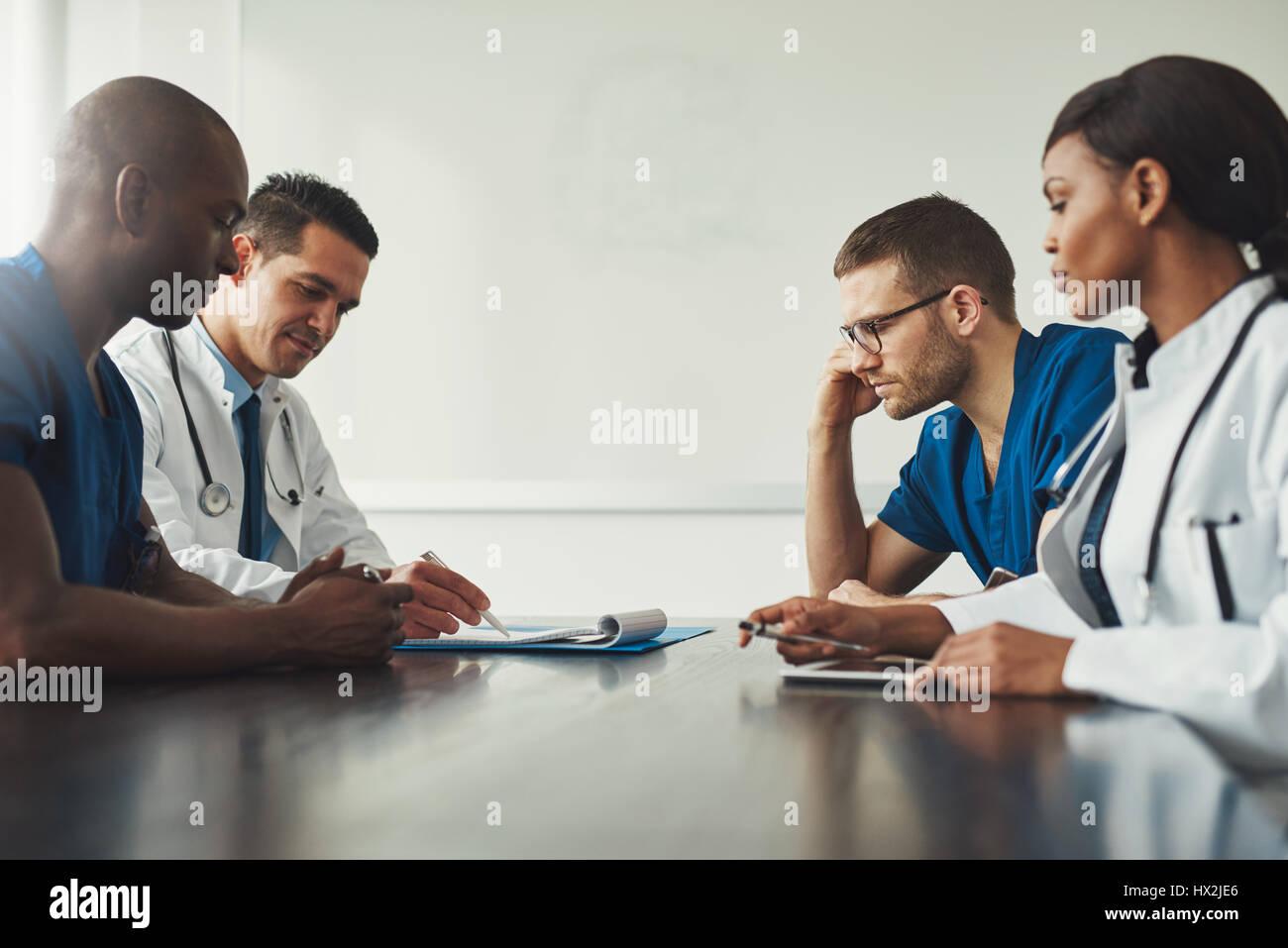 Réunion du personnel médical. Groupe de jeunes gens en blouse blanche et uniforme bleu assis à table Photo Stock