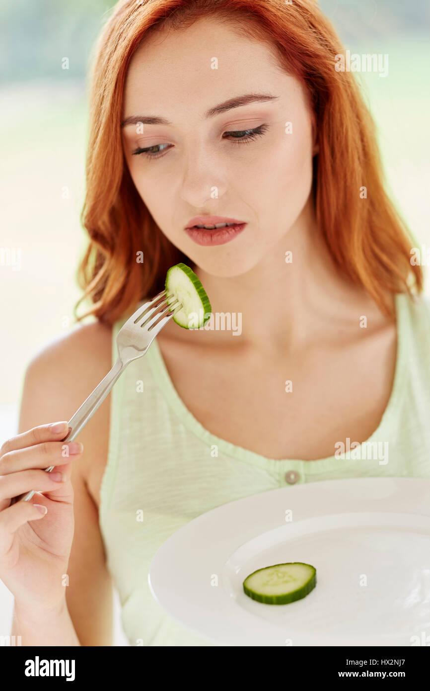 Manger un régime fille tranche de concombre Photo Stock