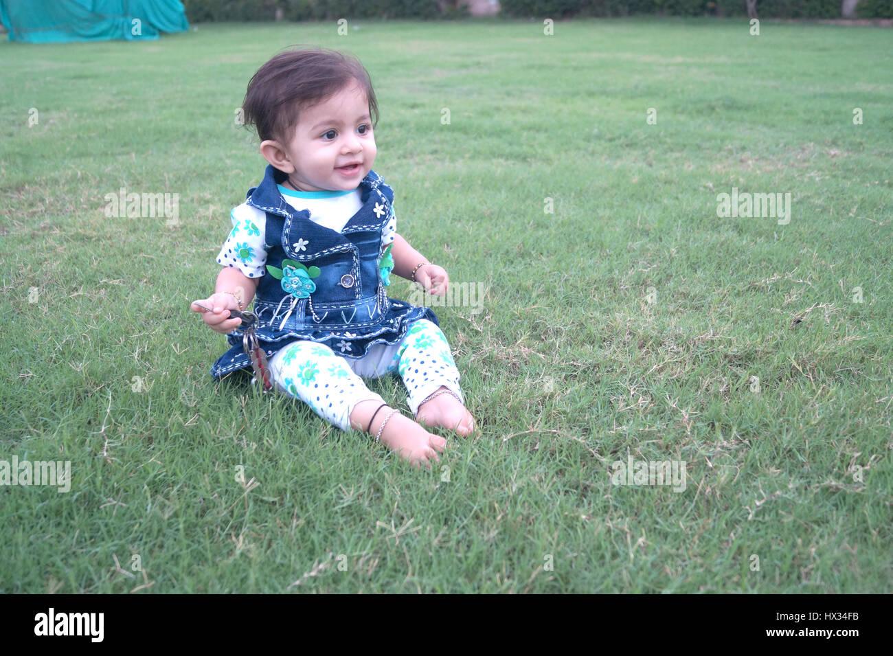 Mignon bébé indien demande à jouer au jardin local quelque part à l'Inde Photo Stock