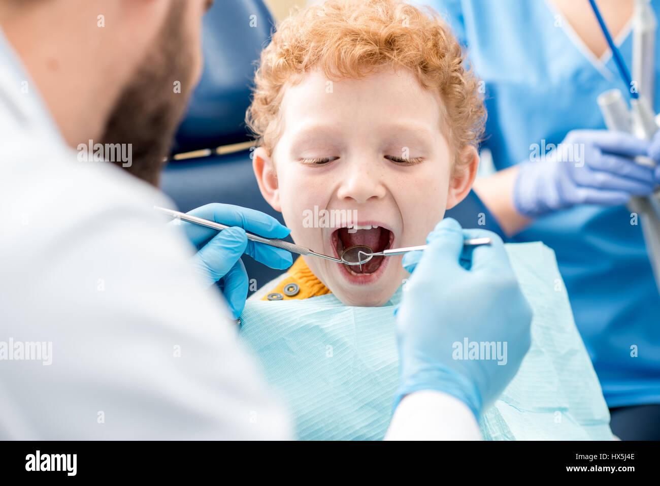 Dentiste pour enfants examinating dents de bébé d un jeune garçon