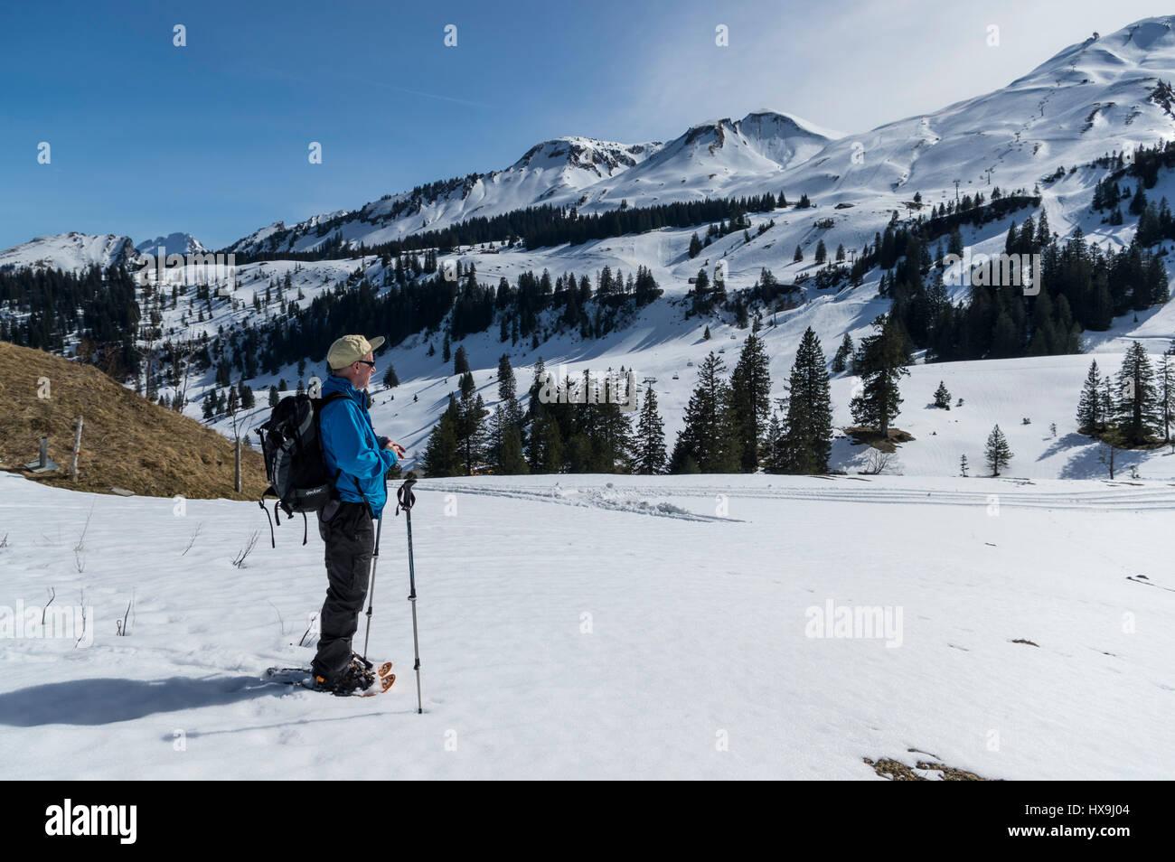 Les hommes d'âge moyen randonneur en raquettes dans les Alpes Suisses, profiter du soleil et panorama des Photo Stock
