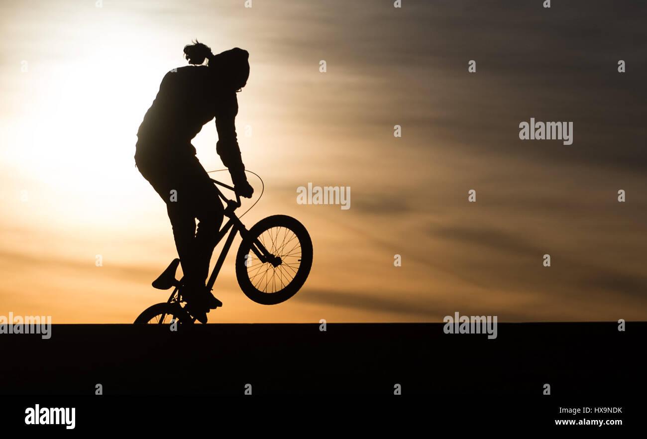 Berlin, Allemagne. Mar 25, 2017. Un biker BMX en action au coucher du soleil à Tempelhofer Feld (lit. Sur le Photo Stock