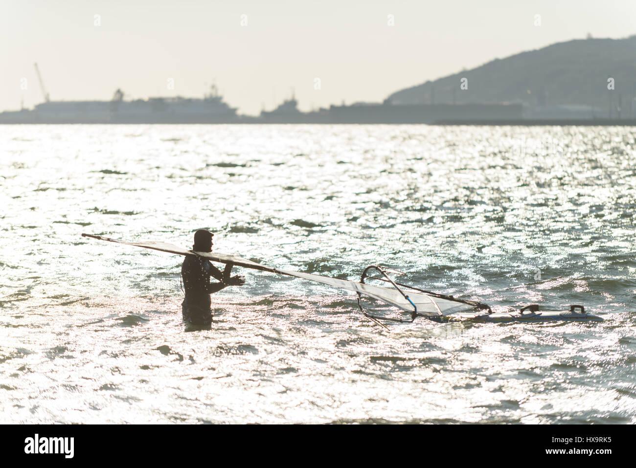 Le port de Portland, Dorset, UK. 26 mars 2017. Un homme de la préparation de son de la planche à voile Photo Stock