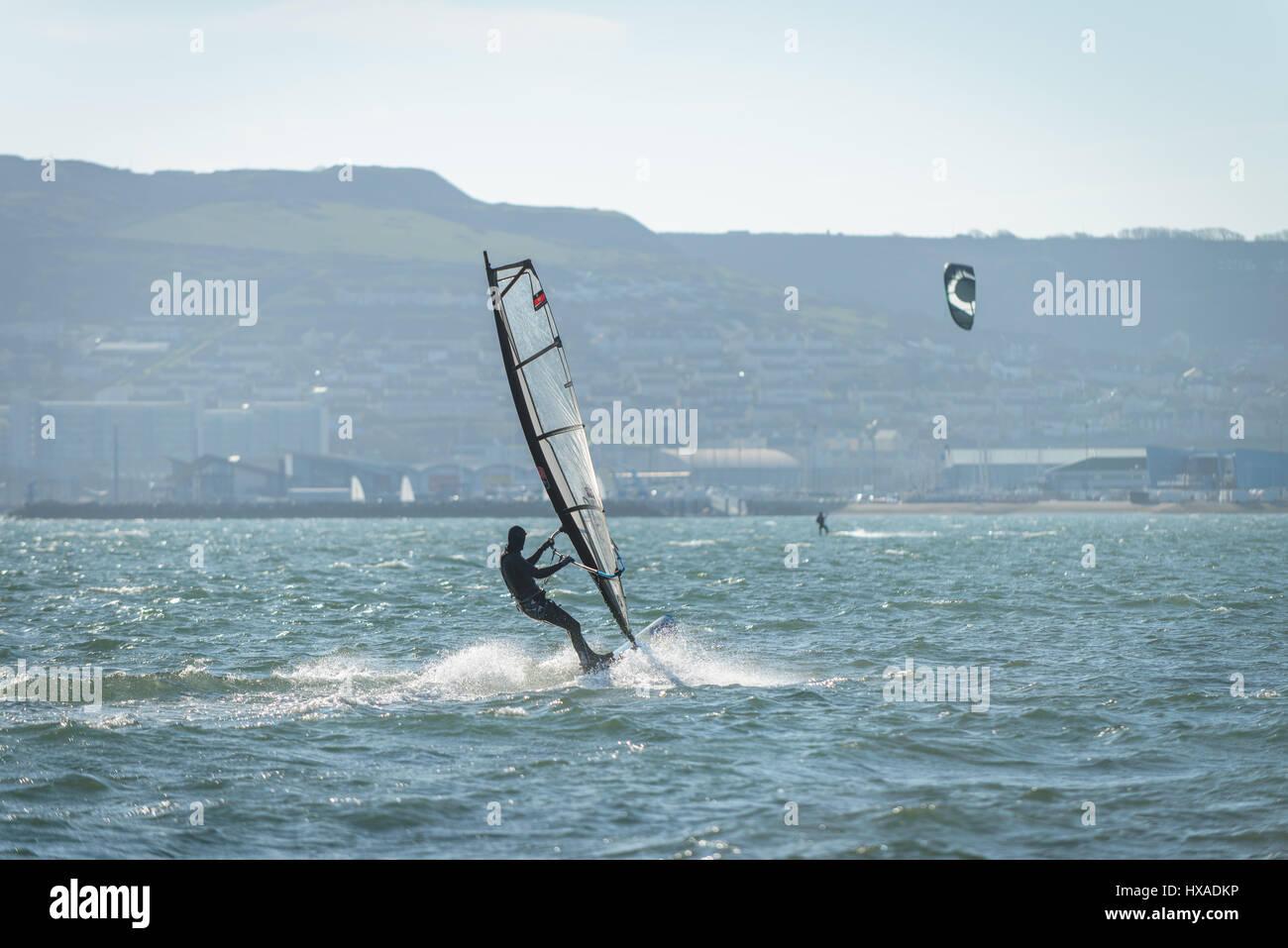 Le port de Portland, Dorset, UK. 26 mars 2017. Un homme planche sur une journée ensoleillée à windy Photo Stock
