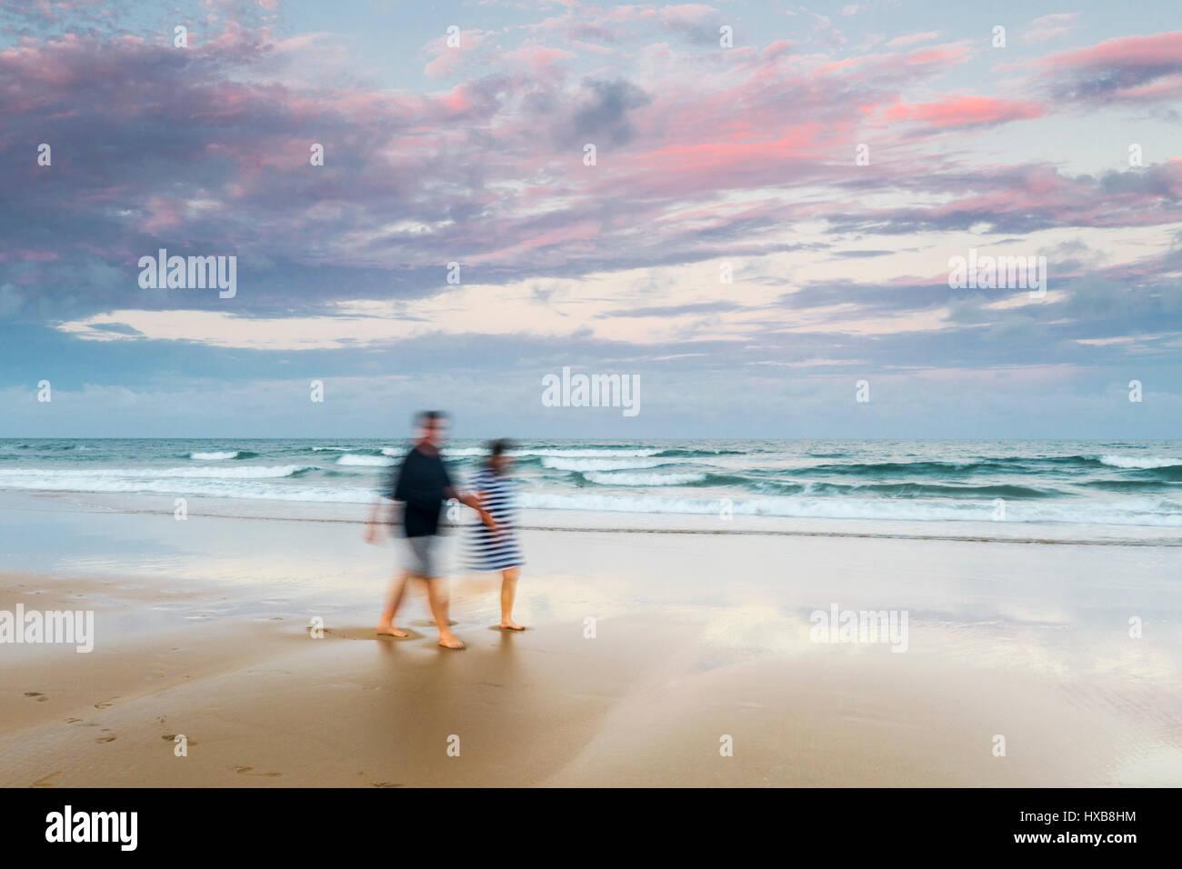 Couple en train de marcher le long des sables de plage de Bargara au coucher du soleil, Bundaberg, Queensland, Australie Banque D'Images