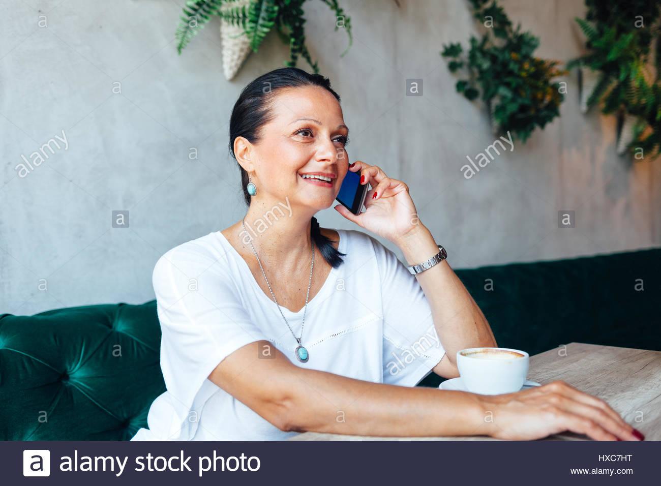 Belle femme d'âge moyen ont un appel téléphonique dans un café Photo Stock
