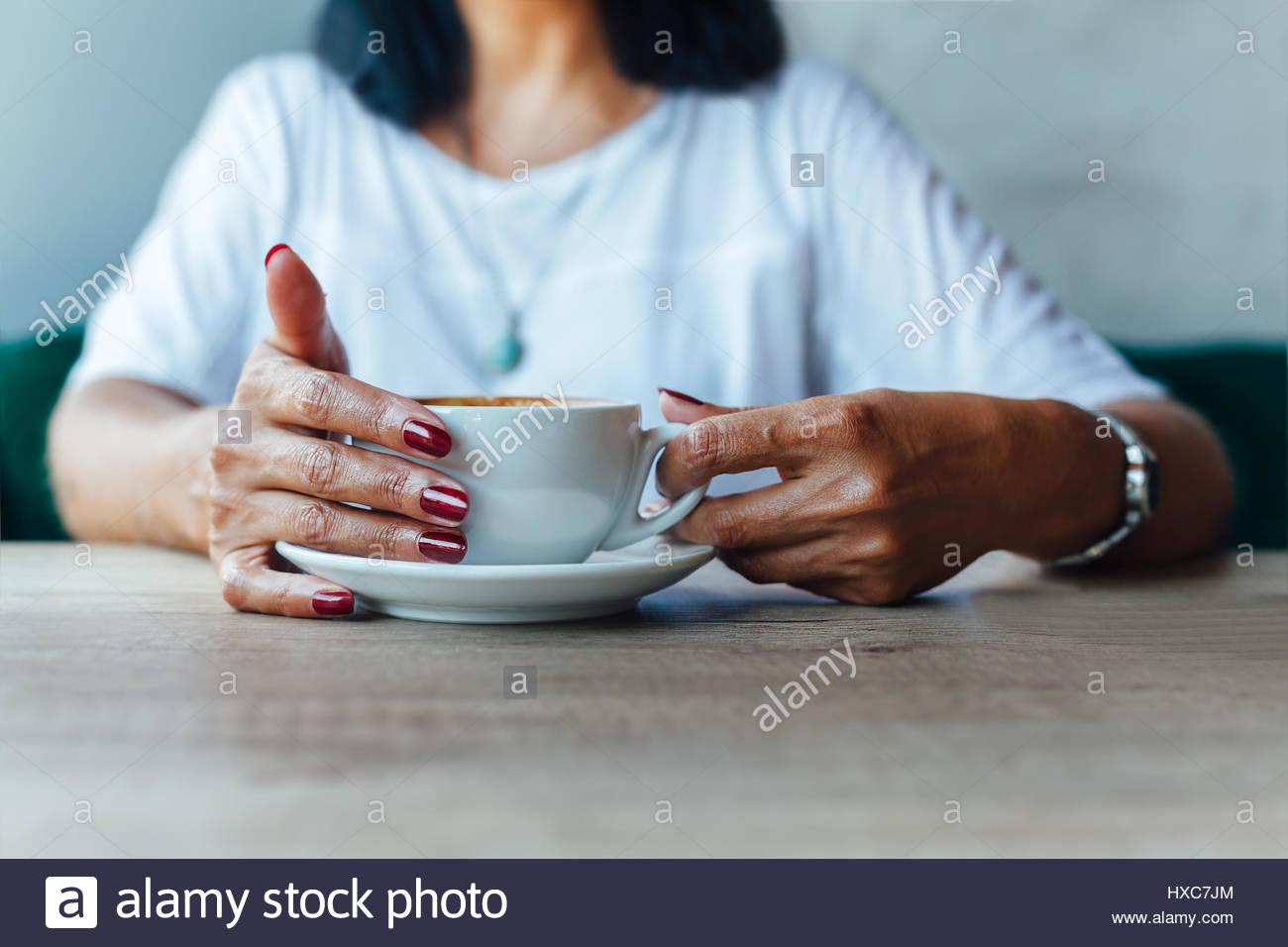 De gros plan femme d'âge moyen avec une tasse de café dans un café Photo Stock