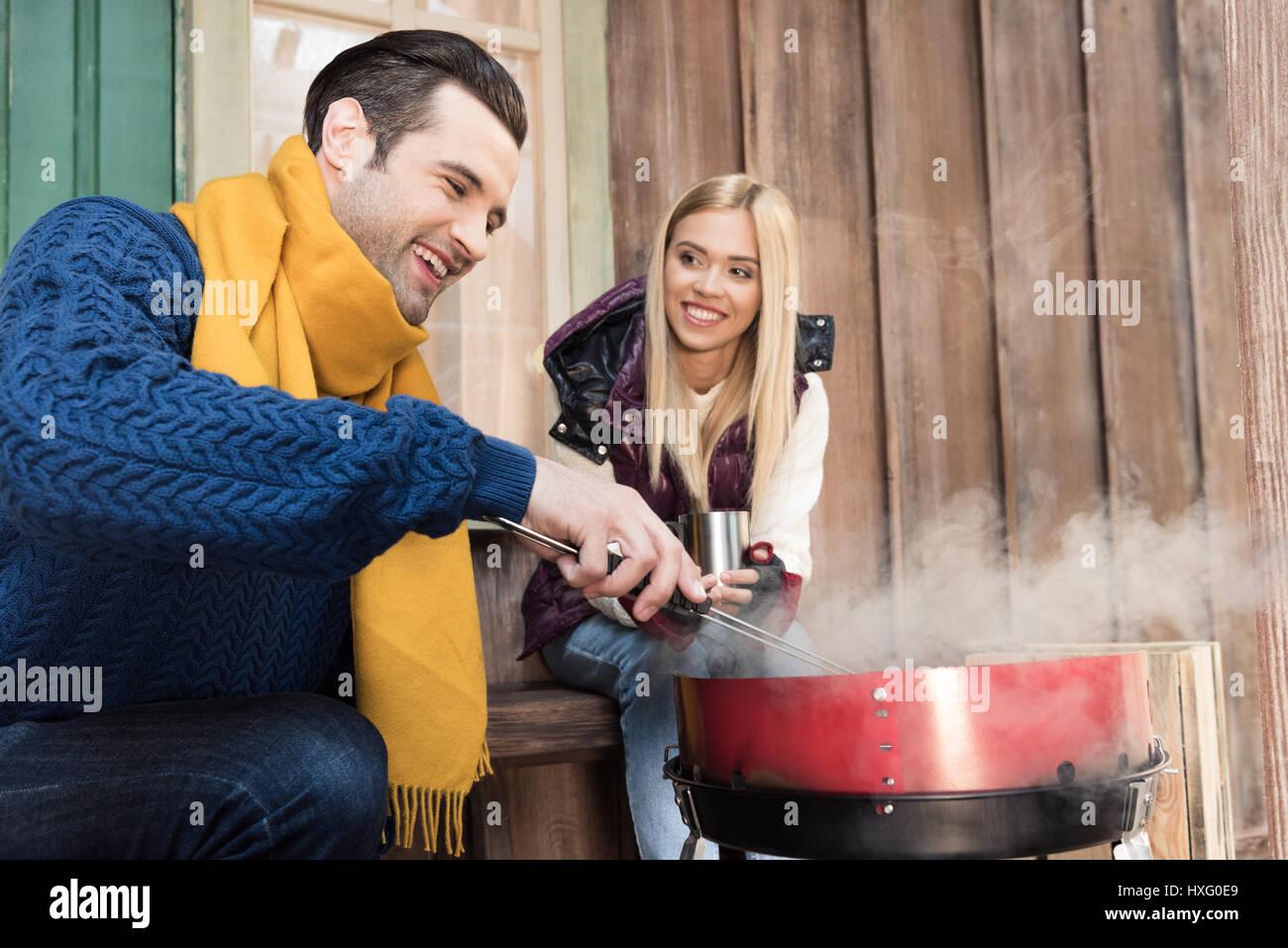 Souriante jeune femme avec boisson chaude à la viande à happy man grilling on porch Banque D'Images