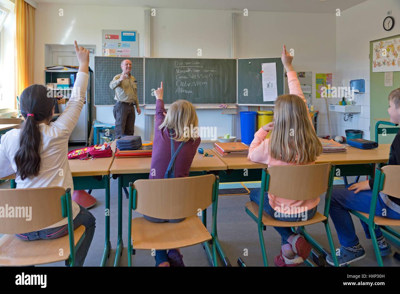 Les enfants lèvent la main à l'école primaire Photo Stock