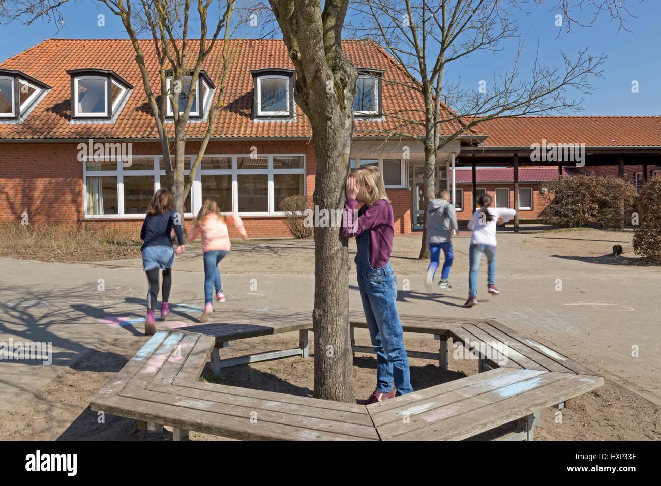 Les enfants à l'école primaire joue à cache-cache pendant les pauses Photo Stock