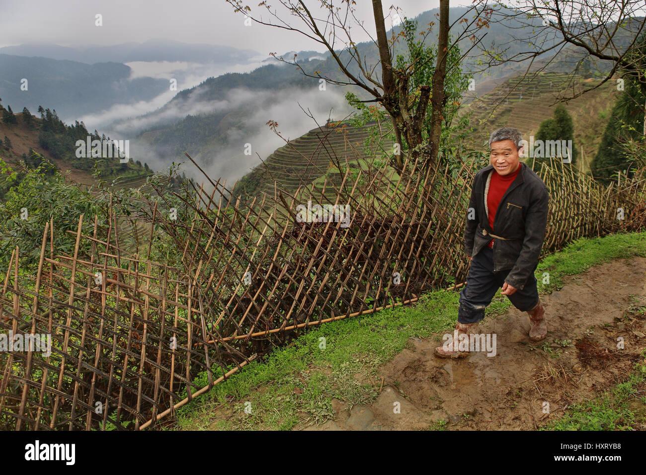 Village Pingan, Province du Guangxi, Chine - 5 Avril 2010: Asian man, portant des bottes en caoutchouc, la Photo Stock