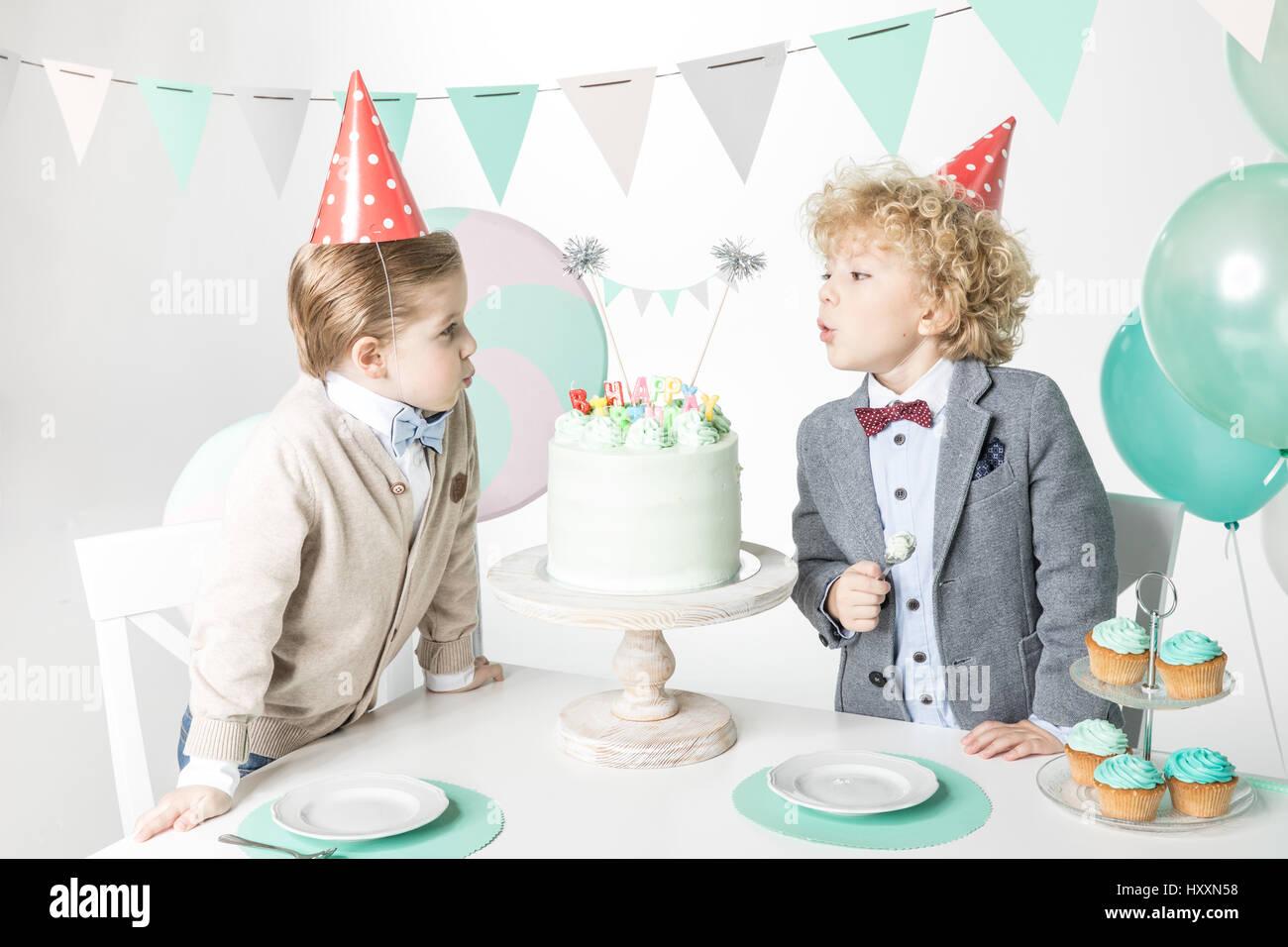 Deux petits garçons en chapeau conique smearing cake Banque D'Images