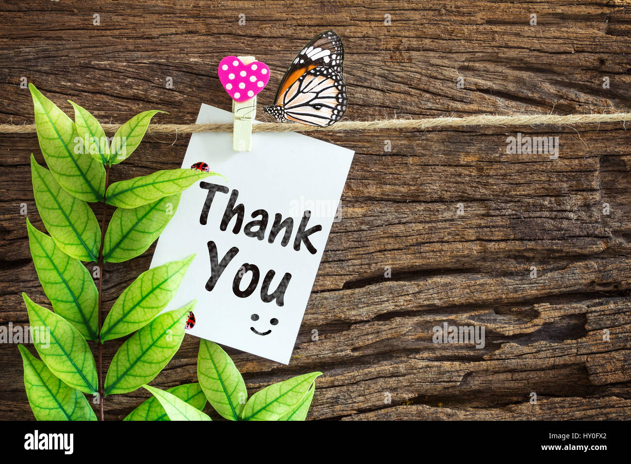 Merci papier remarque suspendu par clips coeur rouge sur fond de bois Photo Stock