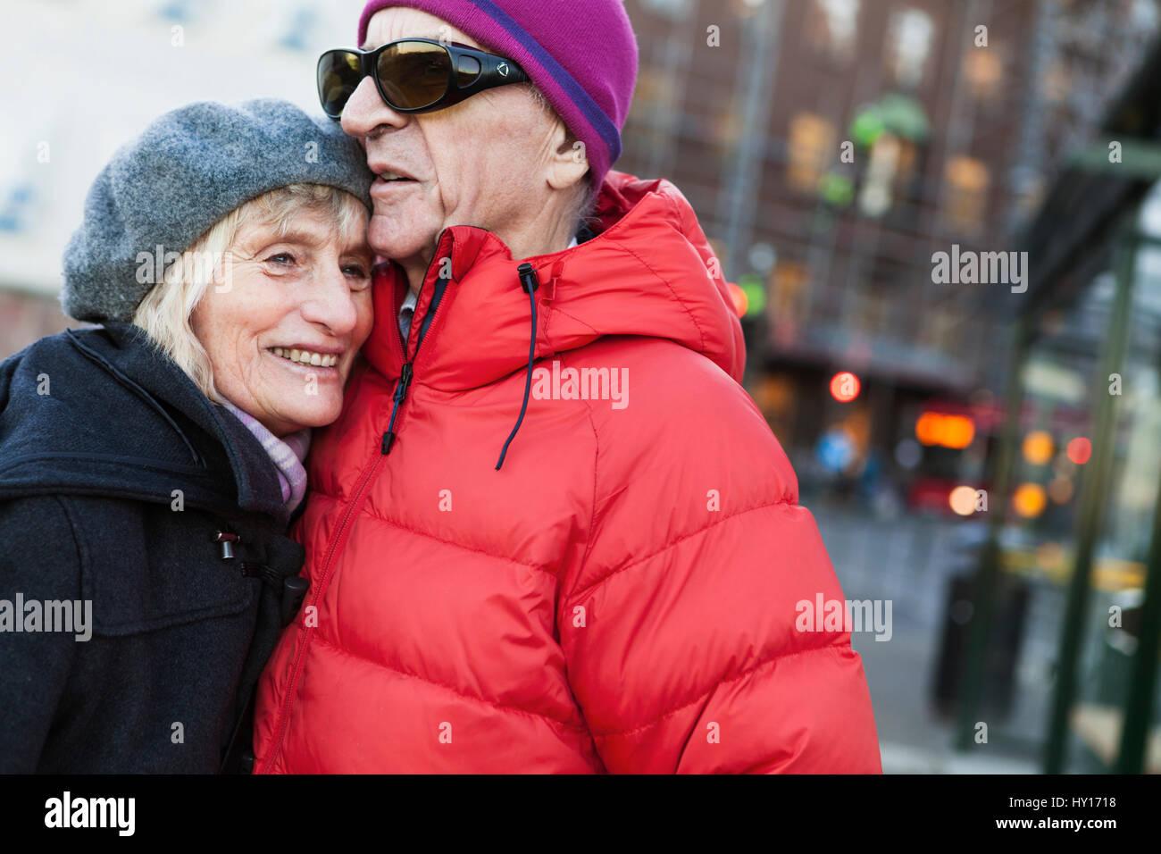 La Suède, Stockholm, Södermalm, senior couple hugging at bus stop Photo Stock