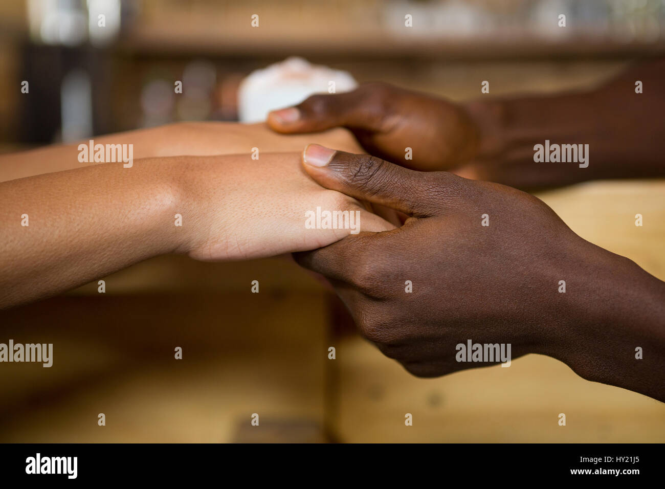 Close-up of multi ethnic couple holding hands in coffee house Photo Stock
