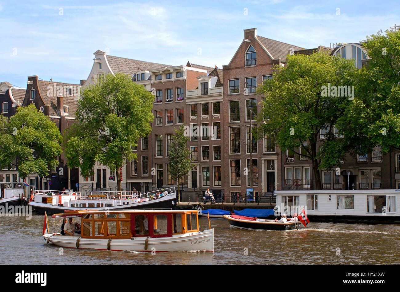 Image de petits bateaux à moteur dans un canal d'eau dans le centre-ville d'Amsterdam, Hollande. Banque D'Images