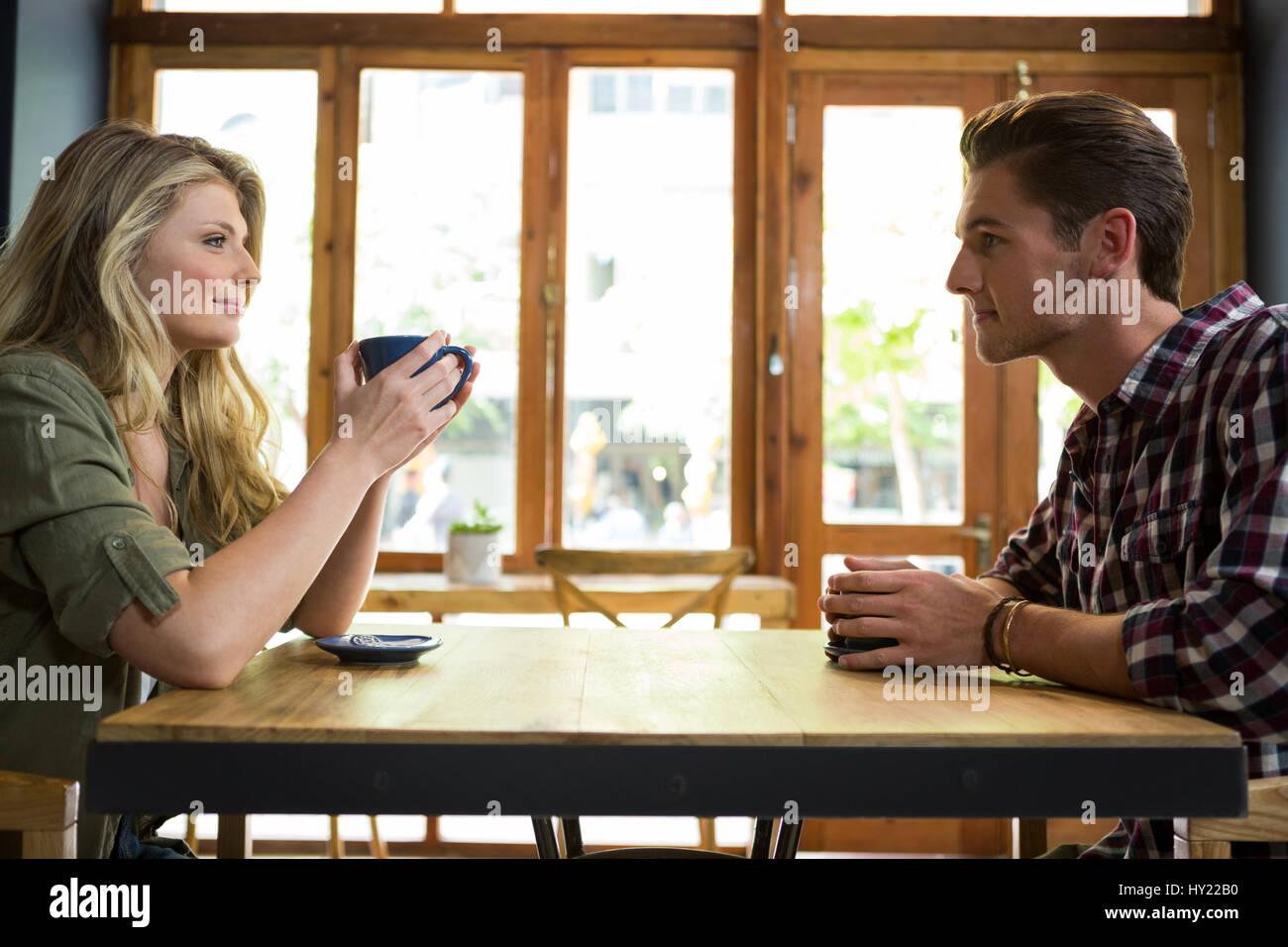 Vue de côté d'aimer young couple having coffee in cafeteria Banque D'Images