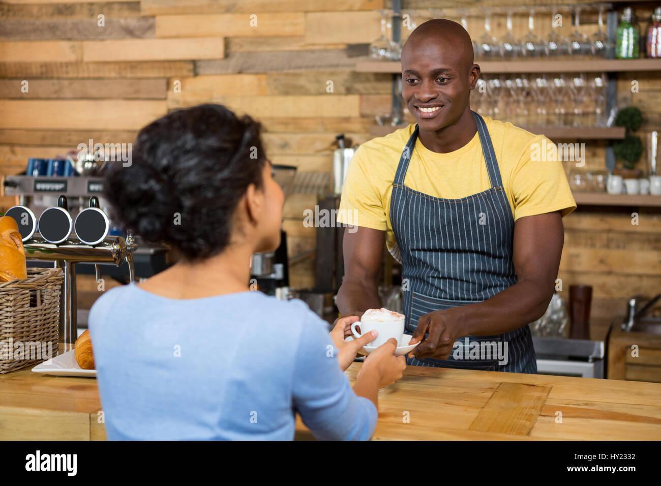 Heureux homme qui sert du café barista au client dans un café Photo Stock