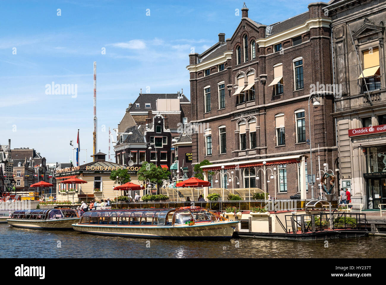 Des bateaux touristiques typiques dans un canal d'eau dans le centre-ville d'Amsterdam, Pays-Bas. Banque D'Images
